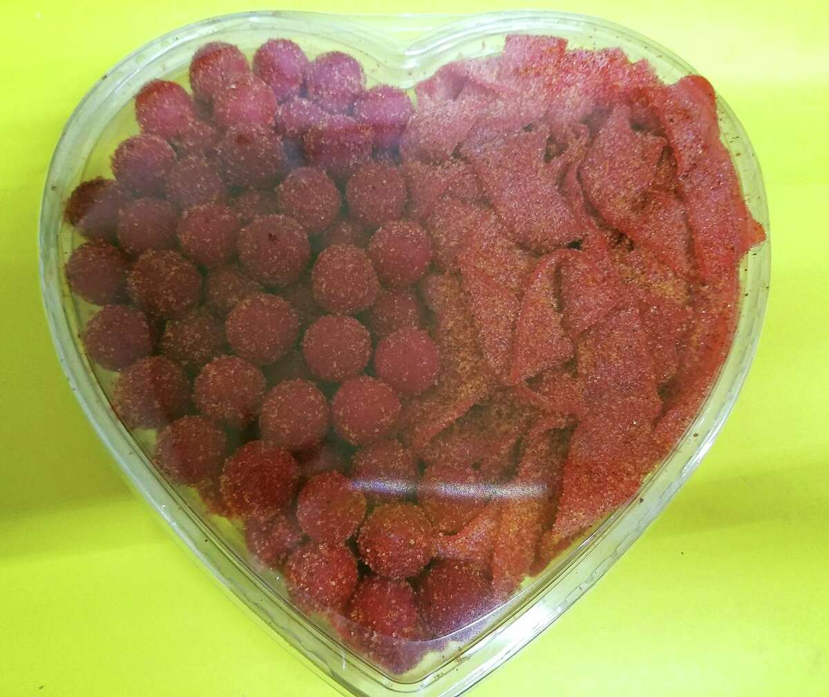 Alamo Candy Co.'s heart-shaped containers filled with Picosito belts and cherry bombs.