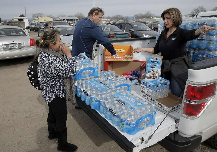 Carmen Corona of Greeley, left, stops to ask for supplies form Tina Kuhl of Sevean Trent, right, who was indepently distributing water and socks at the evacuation center at Silver Dollar Fairgrounds in Chico, Calif., on Monday, February 13, 2017. Several hundred thousand area residents were evacuated down river from the Oroville Dam spillways after officials began to worry there might be an imminent collapse on Sunday. The California Department of Water Resources increased the release from the main spillway to 100,000 cubic feet per second to lower the level of the lake and prevent further damage to the auxiliary spillway. Photo: Carlos Avila Gonzalez, The Chronicle