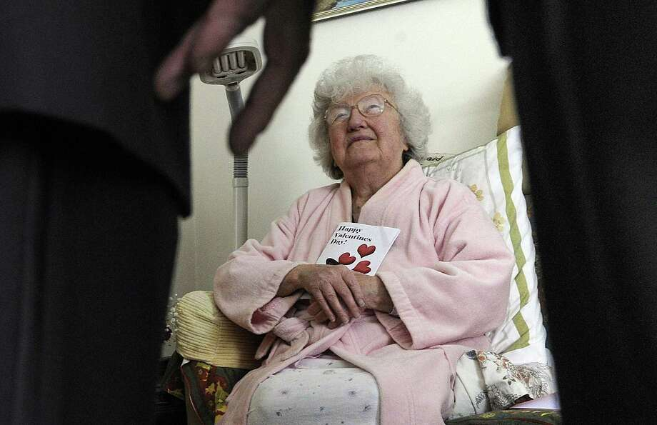 "Libby Kapelari, 87, of Danbury, enjoys a Valentine's visit from a Mad Hatter Chorus quartet Monday, February 13, 2017. One of the songs they sang was rejiggered just for her - ""My Wild Czechoslovakian Rose."" Photo: Carol Kaliff / Hearst Connecticut Media / The News-Times"
