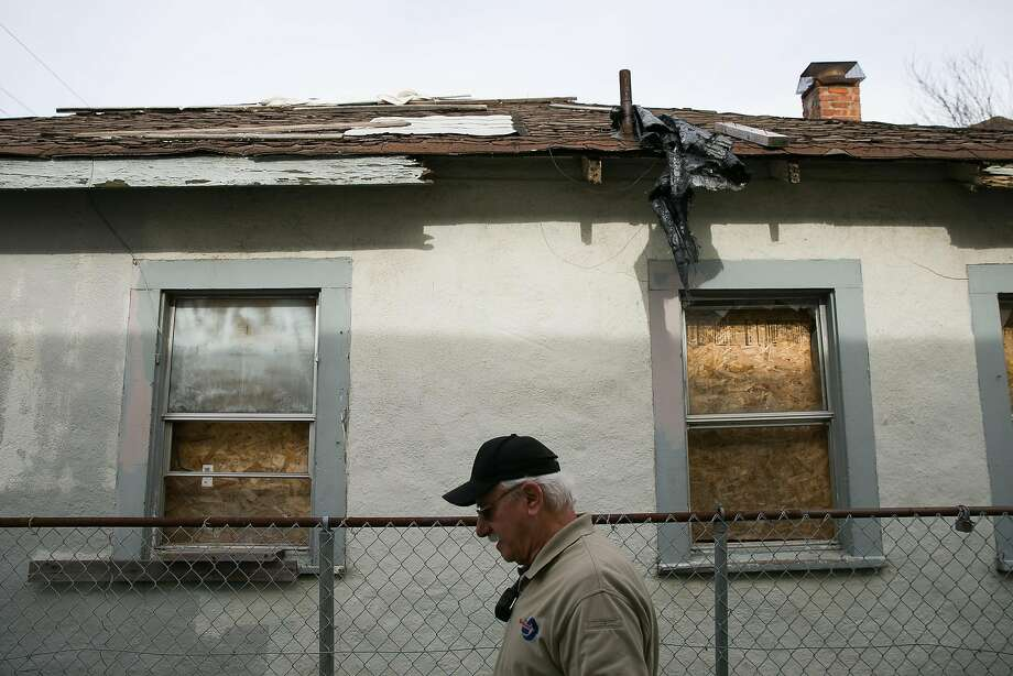 Code enforcement officer David Rogowski walks by a vacant property in Richmond, which has a policy on such buildings. Photo: Mason Trinca, Special To The Chronicle