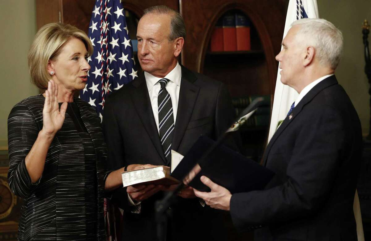 Vice President Mike Pence swears in Education Secretary Betsy DeVos in the Eisenhower Executive Office Building in the White House complex in Washington on Feb. 7, as DeVos' husband Dick DeVos watches.