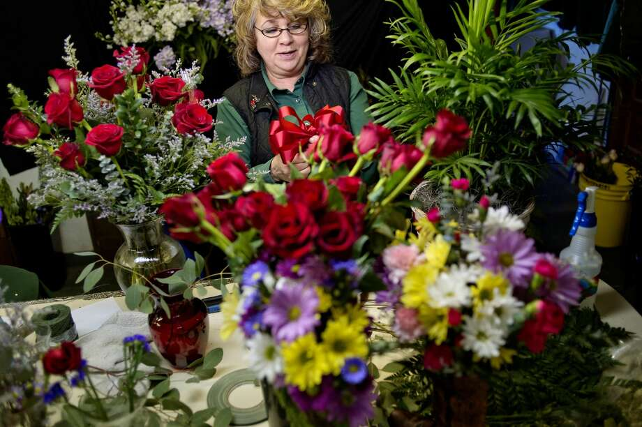 Mary Rheaume works on Valentine's Day orders at Randi's Green Thumb Plants & Flowers on Monday in Midland. Local flower shops are in full gear making arrangements and preparing flowers and orders for customers for Valentine's Day. Photo: NICK KING | Nking@mdn.net