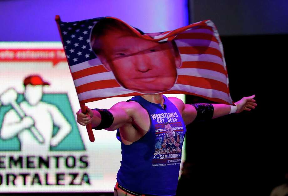 Wrestler Sam Polinsky, aka Sam Adonis, takes the ring Sunday in Mexico City waving an American flag emblazoned with a photo of Donald Trump. Photo: Eduardo Verdugo, STF / Copyright 2017 The Associated Press. All rights reserved.