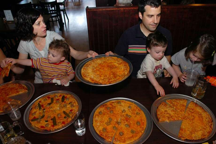 Liza and Joe Liotta, of Fairfield, with (from left), twins sons Beckett and Miller, and daughter Campbell, juggle a table full of pizzas at the new Colony Grill, in Fairfield, Conn. Friday, May 28th, 2010. Photo: Ned Gerard / Connecticut Post