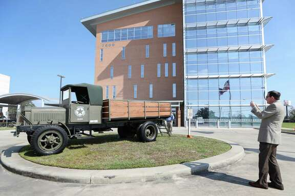 Alan Clark, director of transportation planning for the Houston-Galveston Area Council, shoots a photo of the refurbished World War I surplus truck on display at the Texas Department of Transportation's traveling centennial exhibit.