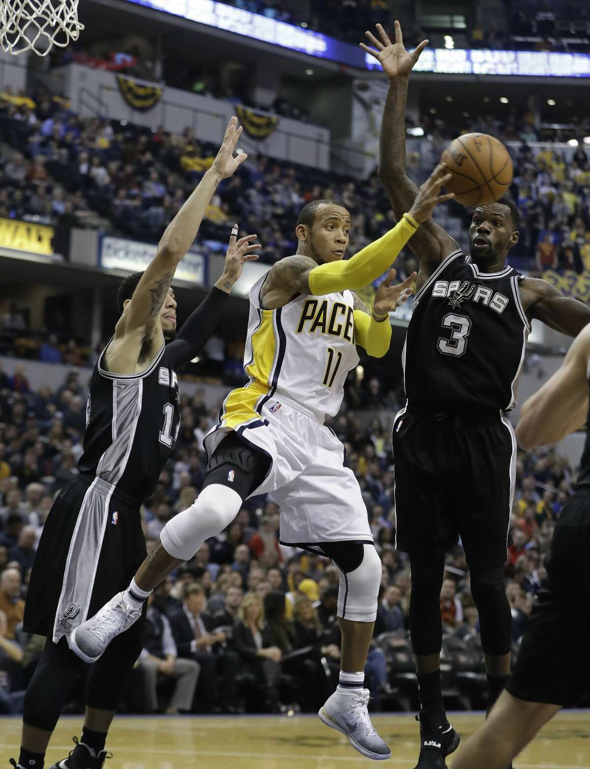 Indiana Pacers' Monta Ellis (11) makes a pass against San Antonio Spurs' Danny Green, left, and Dewayne Dedmon during the first half of an NBA basketball game Monday, Feb. 13, 2017, in Indianapolis. (AP Photo/Darron Cummings)