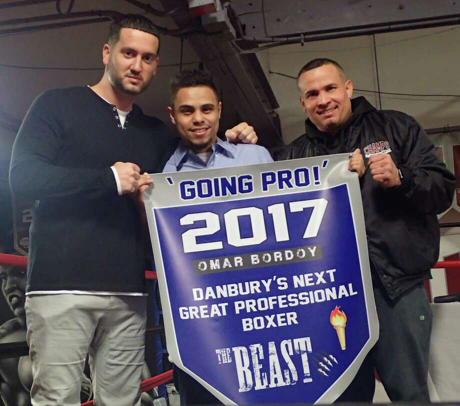 Danbury boxer Omar Bordoy, center, stands with trainer Luis Marichal, right, and Champs Boxing Club co-founder A.J. Galante, left, during the press conference at Champs announcing Bordoy's decision to become a professional fighter on Monday. Photo: Richard Gregory / Richard Gregory