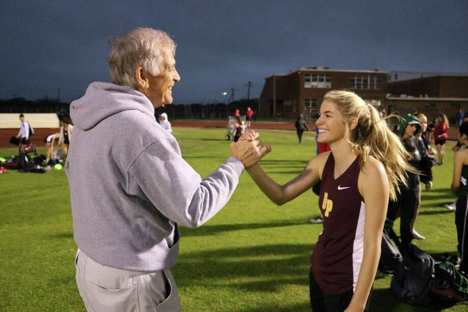 Mike Walker, brought out of retirement to coach the girls team, congratulates one of his athletes during Friday night's 34th annual Kethan Relays. The team opened the new track season with a win. Photo: Robert Avery