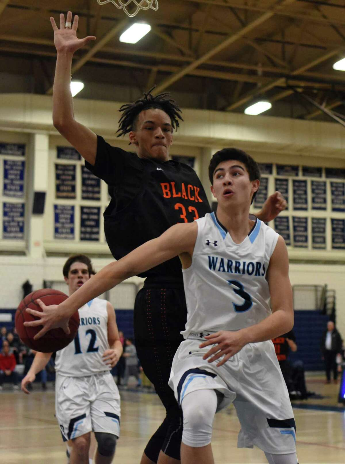 Matt Kronenberg of Wilton (3) dumps a no-look pass behind him for an easy layup during Monday's FCIAC boys basketball game against Stamford. The host Warriors defeated the Black Knights 67-56.