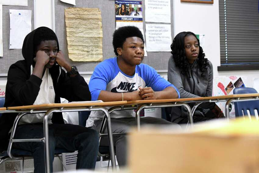 Najm Leggett, left, Al-Shareem Grey and T-Lasha Stokes, right, listen during an Alternative Learning Center social studies class about Joan of Arc on Friday, Feb. 10, 2017, in Albany, N.Y. (Will Waldron/Times Union)