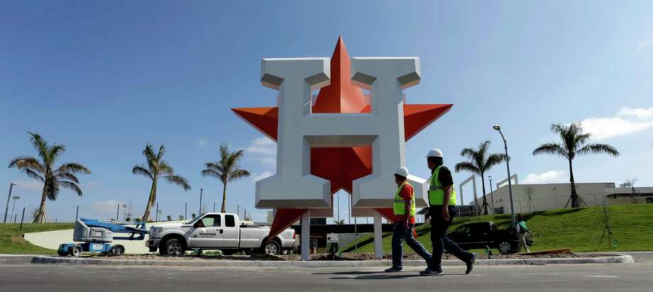 Workers walk past the Houston Astros team logo outside an entrance at the Ballpark of the Palm Beaches, the new spring training facility for the Astros and Washington Nationals, Monday, Feb. 13, 2017, in West Palm Beach, Fla. Astros pitchers and catchers are scheduled to report Tuesday.(AP Photo/David J. Phillip) Photo: David J. Phillip, Associated Press / Copyright 2017 The Associated Press. All rights reserved.