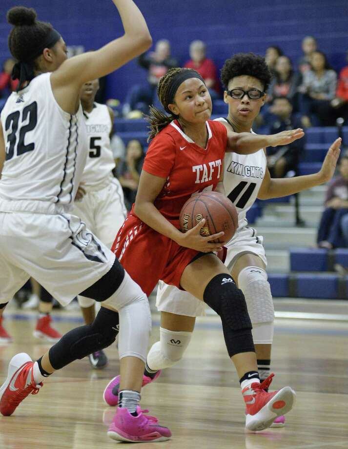 Taft guard Tierra Tullis, center, drives past Steele guard Kavin Johnson (11) and Antonia Anderson during the first half of a playoff high school basketball game, Monday, Feb. 13, 2017, at Veterans Memorial High School in San Antonio. (Darren Abate/For the San Antonio Express-News) Photo: Darren Abate, FRE / San Antonio Express-News