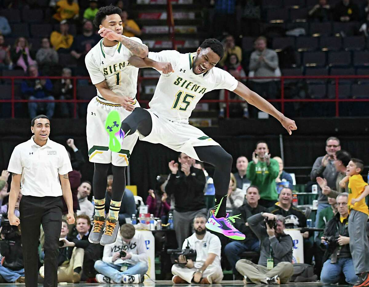 Siena's Marquis Wright, left, and Nico Clareth celebrate after Wright sinks a three pointer at the very end of the first half during a basketball game against Monmouth at the Times Union Center on Monday, Feb. 13, 2017 in Albany, N.Y. (Lori Van Buren / Times Union)
