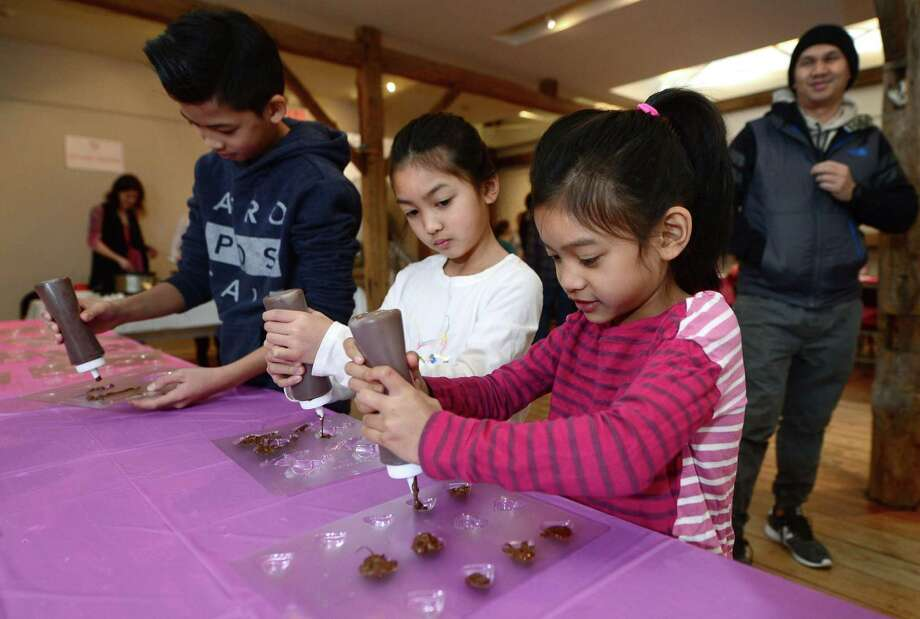 Jacob,  Jada and Janae Lim, 11, 7 and 5, make chocolates during the Make Your Own Valentine's Day Chocolates! Workshop Saturday, February 11, 2017 at the Wilton Historical Society in Wilton, Conn. The Wilton Historical Society offers the very popular chocolate-making workshop annually where kids in grades K-8  make delicious, professional-looking chocolates and a decorated box to put them in during the one hour session. Photo: Erik Trautmann / Hearst Connecticut Media / Norwalk Hour