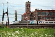 An Amtrak Acela train travels past the former Remington Arms factory, and Shot Tower, in Bridgeport, seen from the vacant Father Panik Village property. A new commuter rail station is planned near this location, tentatively called Barnum Station.