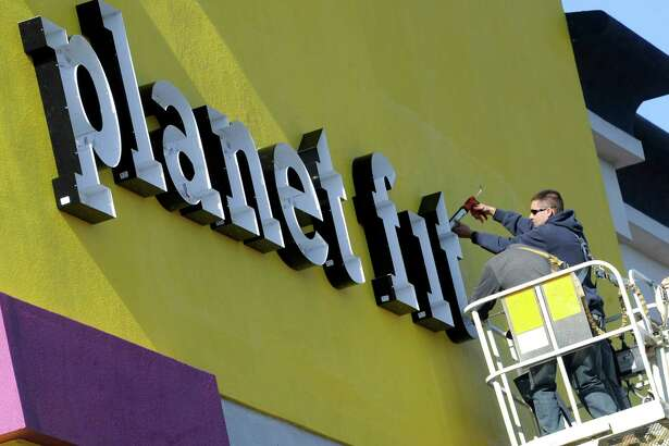 Workers install the new sign at Planet Fitness Thursday, Nov. 14, 2014. The new gym will be opening soon in the Borders spot at 110 Federal Road in Danbury, Conn.