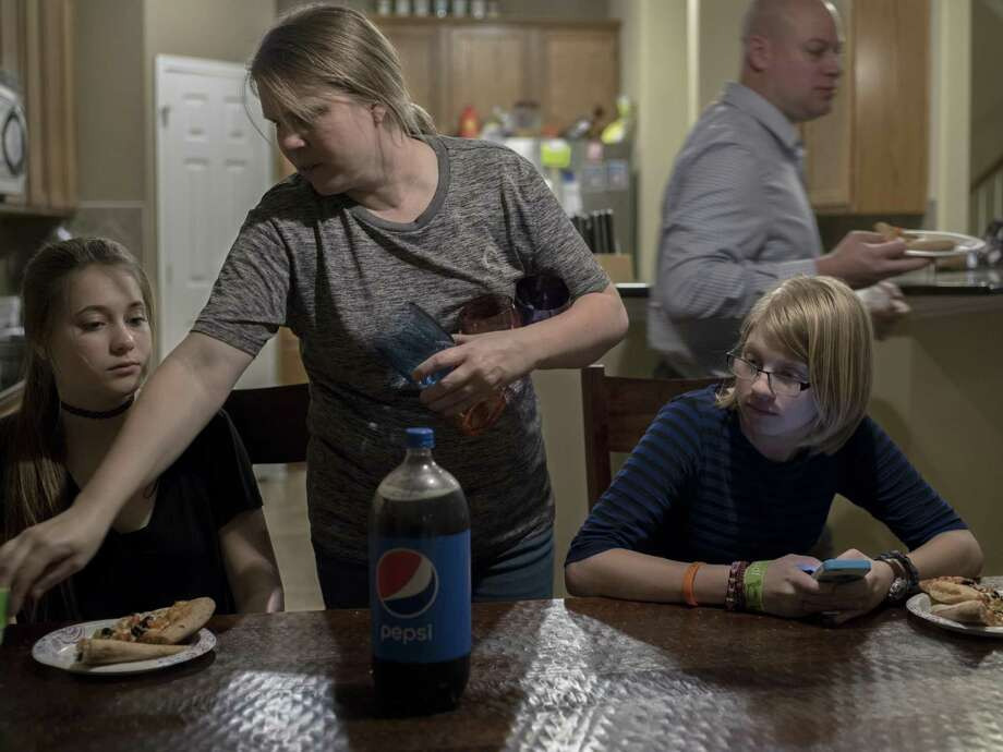 Military child Alyssa Scott, 17, who is a senior at Stacey Junior-Senior High School, right, uses her smartphone while she eats dinner with her father, Henry Scott, right, mother, Dylan, second left, and sister, Ashlyn, 13, left, in San Antonio, Texas on January 10, 2017. Scott's family moved to San Antonio from California late this past year. Photo: Matthew Busch /For The San Antonio Express-News / © Matthew Busch
