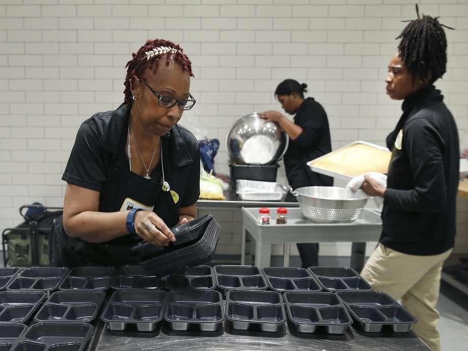 Renee Jackson, Regina Edwards and Jackson's daughter Tyesha Davis prepare catered school lunches. Photo: Paul Chinn, The Chronicle