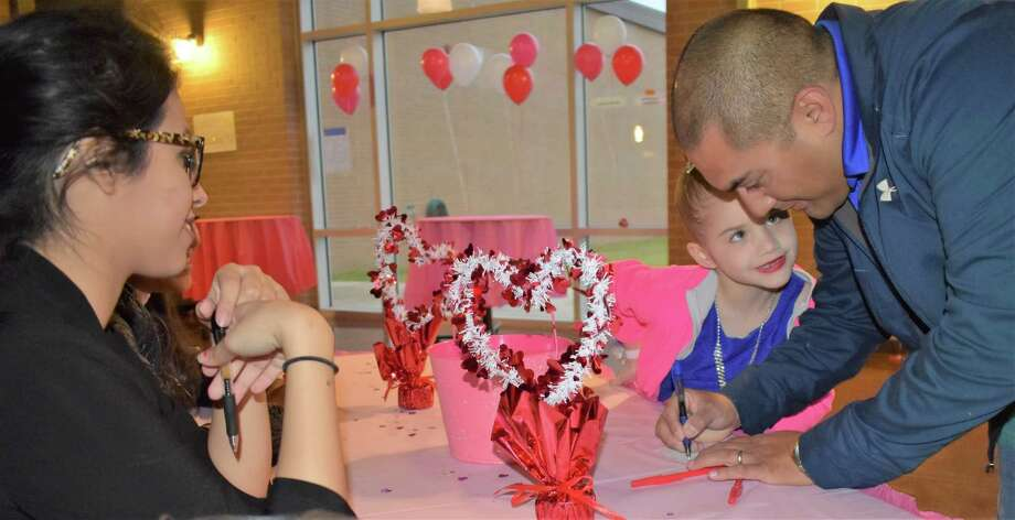 Needville High School Theatre Arts student Keithly Vite welcomes 6-year-old Jillian Hernandez and her dad, Rudy, to the annual Valentine-themed Daddy-Daughter Dance on Feb. 3 in the high school cafeteria. Photo: Needville ISD