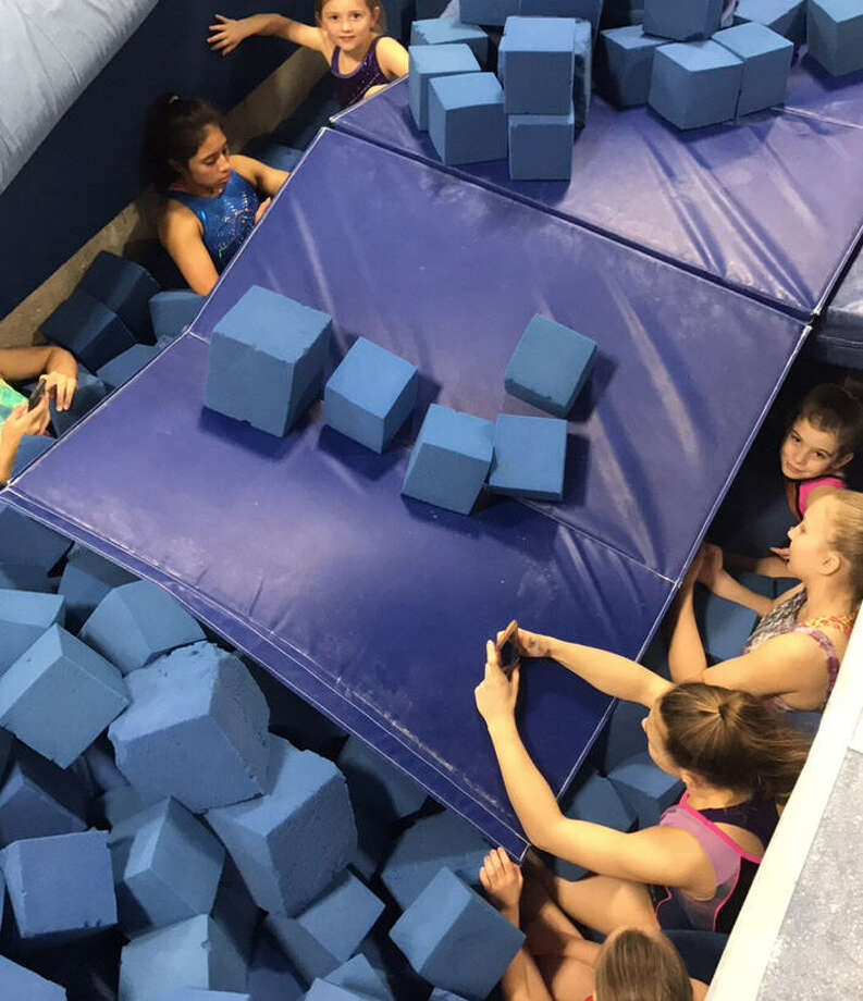 Gymnastics students at Pearland Elite Training Center shelter in place in a gigantic foam pit during stormy weather Tuesday, Feb. 14, 2017. (Photo: Nick Cedillo)