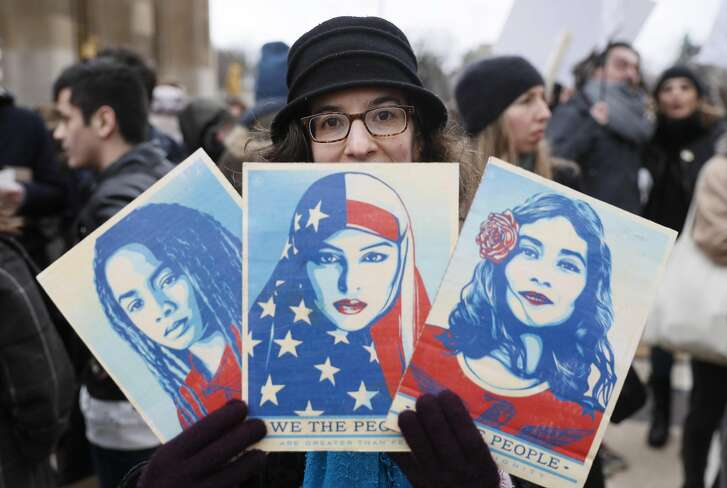 """TOPSHOT - An anti-Trump protester hold signs during a demonstration against Trump's policies in front of the Eiffel Tower in Paris, on February 4, 2017.  US President Donald Trump lashed out on February 4, 2017 at a court ruling suspending his controversial ban on travelers from seven Muslim countries, dismissing it as """"ridiculous"""" and vowing to get it overturned. The order blocking the ban, issued late on February 3, 2017 by Seattle US District Judge James Robart, is valid across the United States, pending a full review of a complaint filed by Washington state's attorney general. / AFP PHOTO / THOMAS SAMSONTHOMAS SAMSON/AFP/Getty Images"""