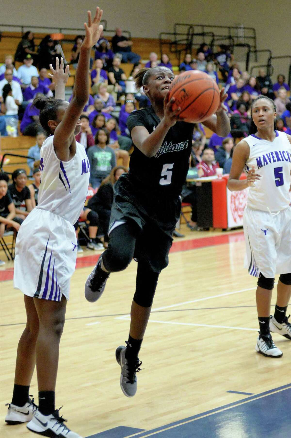 Taelor Purvis (5) of Hightower attempts a shot during the second half of the girls Bi-District playoff game between the Hightower Hurricanes and the Morton Ranch Mavericks on Monday February 13, 2017 at Alief Taylor High School, Houston, TX.