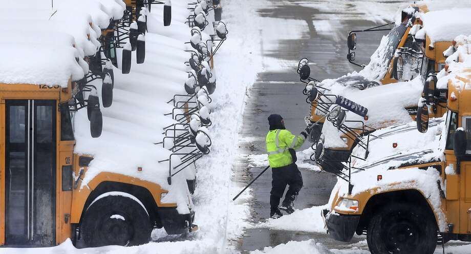 A worker clears snow off school buses Monday after schools were closed due to a snowstorm in Manchester, N.H. Photo: Charles Krupa, Associated Press