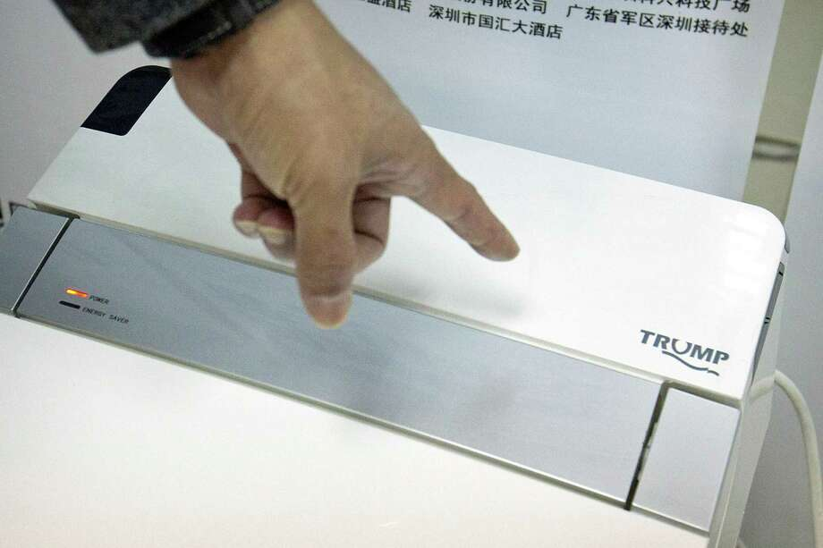 Zhong Jiye, a co-founder of Shenzhen Trump Industrial Co., points to the logo on one of his firm's high-end Trump-branded toilets at the company's offices in Shenzhen in southern China's Guangdong Province. U.S. President Donald Trump is poised to receive something that he had been trying to get from China for more than a decade: trademark rights to his own name. The makers of Trump-branded luxury toilets say they will defend their brand, even if it means taking on the U.S. president. Photo: Mark Schiefelbein /Associated Press / Copyright 2017 The Associated Press. All rights reserved.