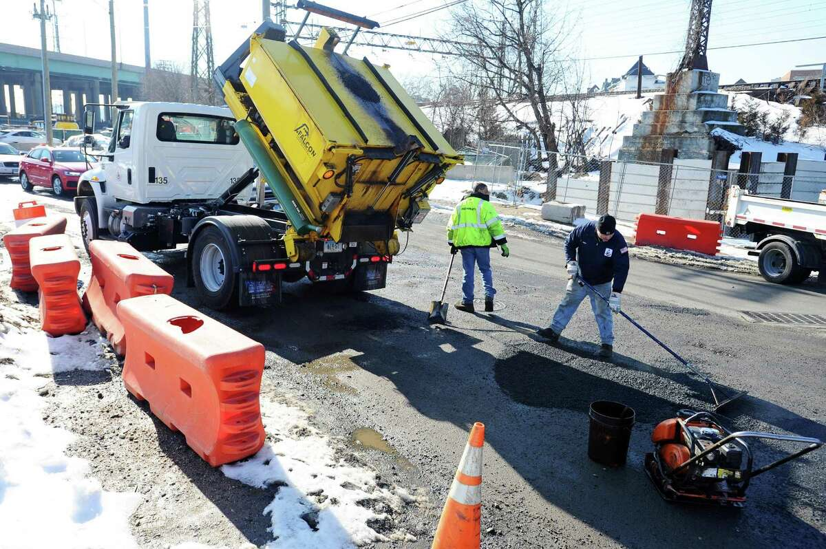 A city crew fills potholes on Myrtle Ave., on the corner of E. Main St., in Stamford, Conn. on Tuesday, Feb. 14, 2017.