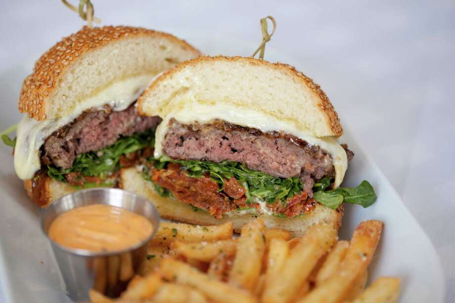 The Bello Burger on a homemade bun with provolone, caramelized onions, slow-roasted tomato,arugula, and white balsamic vinaigrette is one of the new menu items at Tony Vallone's Ciao Bello restaurant. Ciao Bello has a new executive chef, Alan Paryzek. Photo: Vallone Restaurant Group / (C) 2016 STP Images Photography Studio