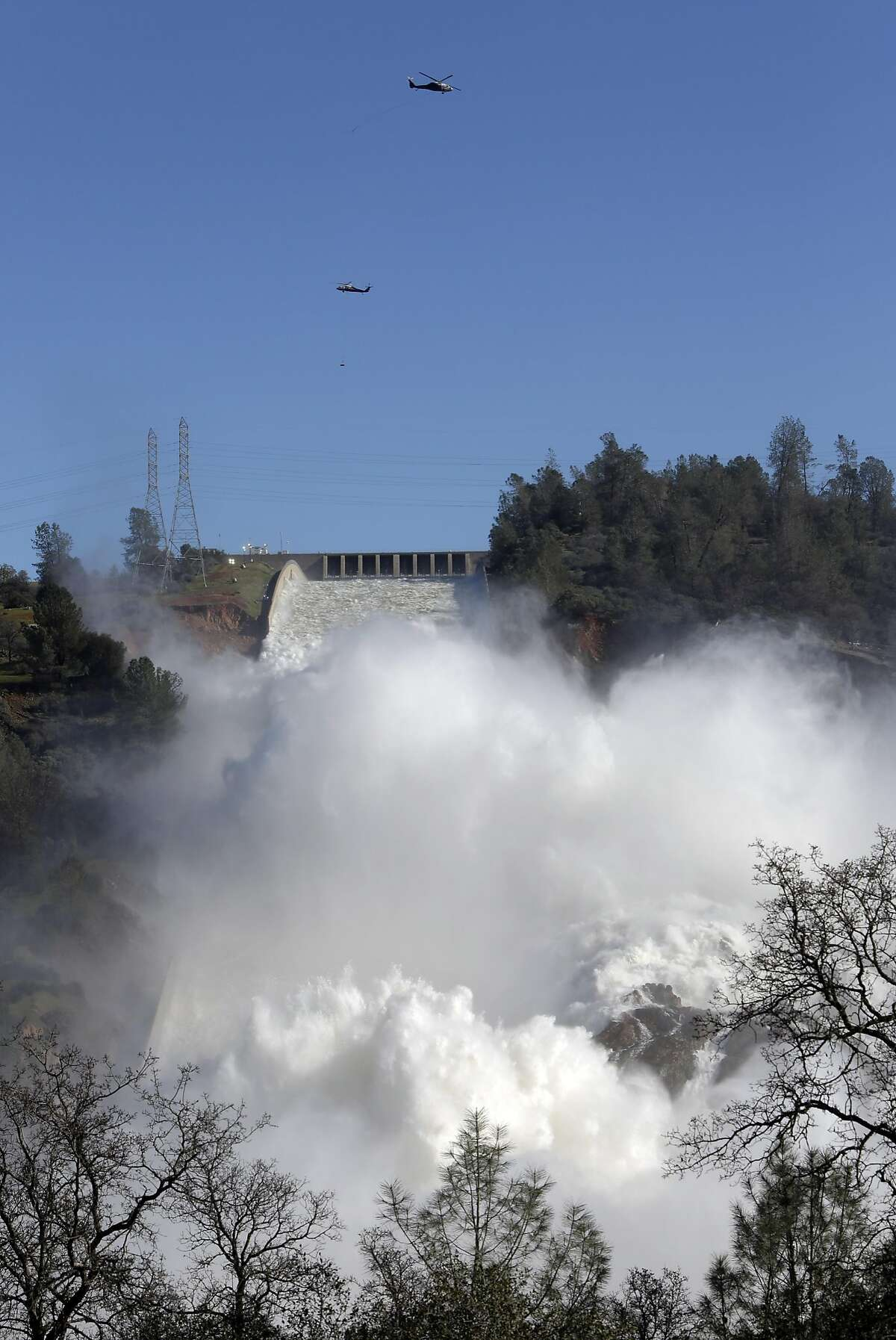 Helicopters continue to stabilize the emergency spillway next to the main Oroville Dam spillway as water is released on Tuesday Feb. 14, 2017, in Oroville, Ca.