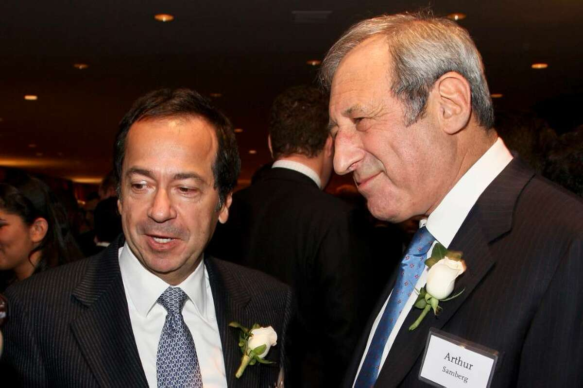 """John A. Paulson, president of Paulson & Co., left, speaks with Arthur """"Art"""" Samberg, chairman of Pequot Capital Management Inc., during the UJA Federation of New York's annual Wall Street Dinner in New York, U.S., on Wednesday, Dec. 16, 2009. Some observers feel that Paulson, manager of the world's third biggest hedge fund, makes bets that are too big and overly risky. Samberg's Wilton-based Pequot, once the biggest hedge fund, is being wound down. Photographer: Rick Maiman/Bloomberg *** Local Caption *** John A. Paulson; Arthur """"Art"""" Samberg"""