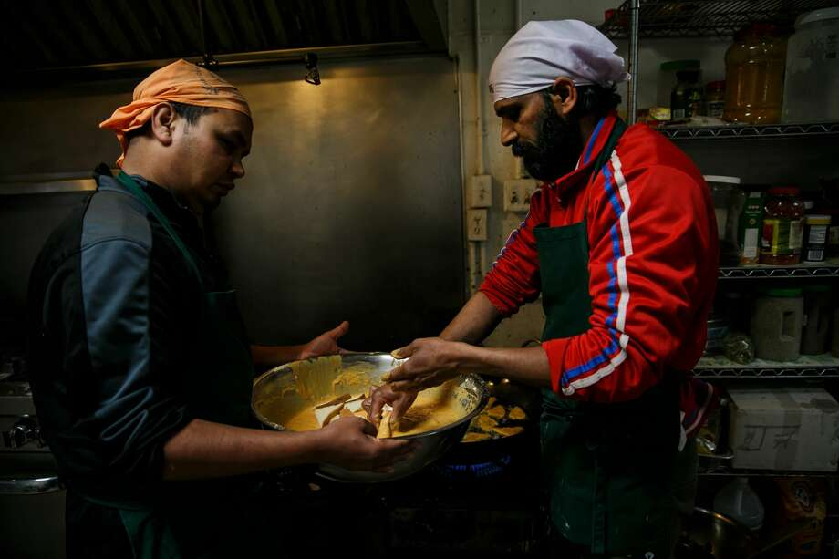 Ashok Kumar, left and Raj Kumar, right, prepare breakfast at the Shri Guru Ravidass, a Sikh temple that has opened its doors for all evacuees of the Oroville Dam crisis, on February 14, 2017 in Rio Linda, California. (Photo by Marcus Yam / Los Angeles Times via Getty Images) Photo: Marcus Yam/LA Times/Getty Images