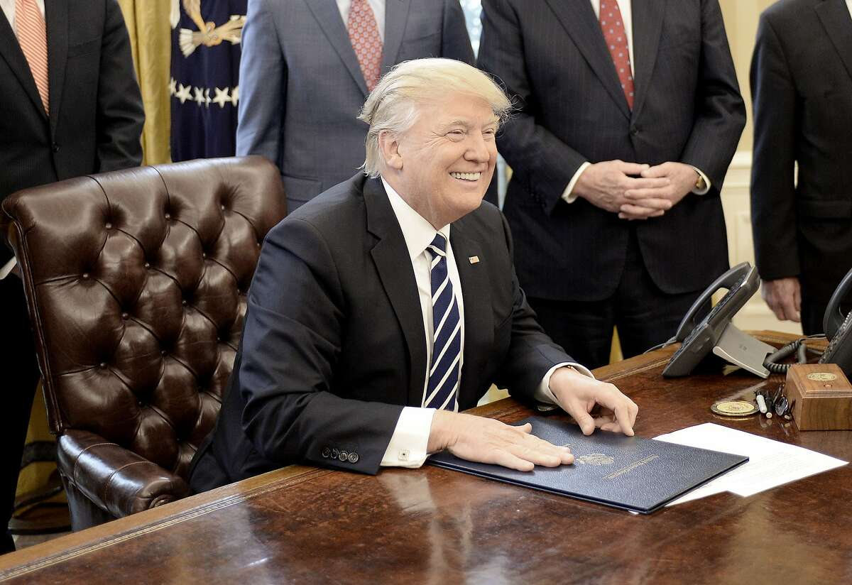 WASHINGTON, D.C. - FEBRUARY 14: (AFP-OUT) U.S. President Donald Trump smiles after signing H.J. Res. 41 in the Oval Office of the White House on February 14, 2017 in Washington, DC. The resolution nullifies a rule in the Dodd-Frank Act that