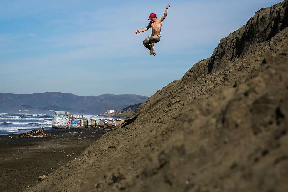 Maurice Green jumps off of a small bluff at Ocean Beach in San Francisco, California, on Tuesday, Feb. 14, 2017. Photo: Gabrielle Lurie, The Chronicle