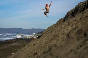 Maurice Green jumps off of a small bluff at Ocean Beach in San Francisco, California, on Tuesday, Feb. 14, 2017.