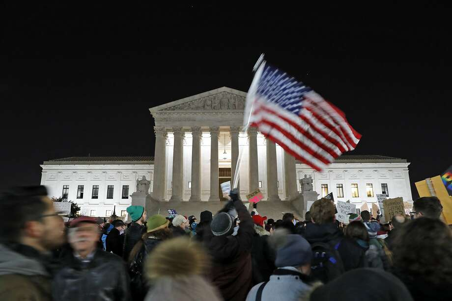 A protester waves an American flag in front of the Supreme Court during a protest about President Donald Trump's recent executive orders, Monday, Jan. 30, 2017 in Washington. (AP Photo/Alex Brandon) Photo: Alex Brandon, Associated Press
