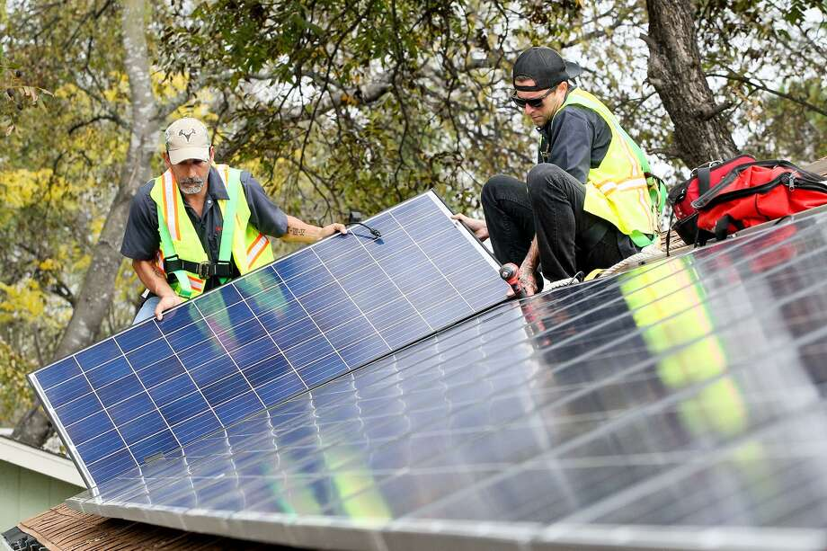 Solar installers put panels on the roof of a home in San Antonio. Photo: San Antonio Express-News File Photo / Express-News 2015
