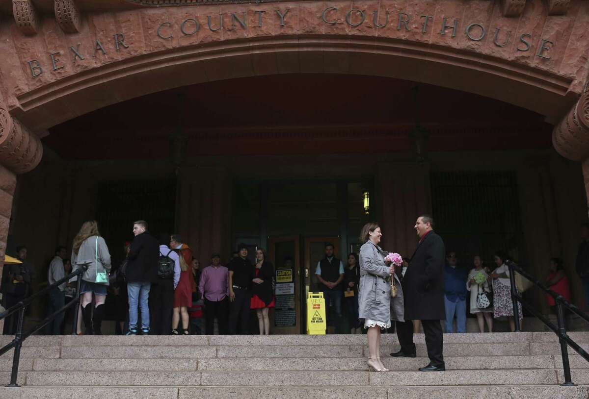 Amanda Torres, 40, and Michael Flores, 42, wait for the start of the 10 a.m. Valentine's Day weddings in front of the Bexar County Courthouse, Feb. 14, 2017. Around 26 couples braved the cold winds to marry during the ceremony conducted by Bexar County Clerk Gerard Rickhoff. Torres and Flores are longtime friends.