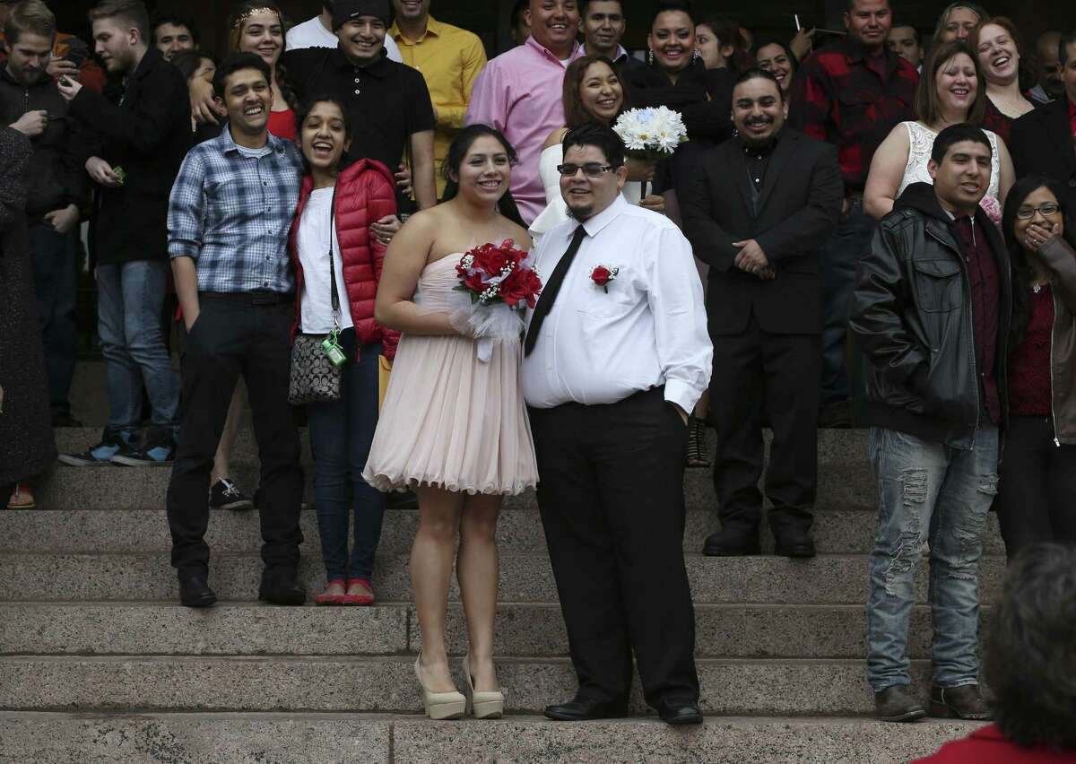 Savannah Rodriguez, 20, and Zachary Rodriguez, 21, wait for the start of the 10 a.m. Valentine's Day weddings in front of the Bexar County Courthouse, Feb. 14, 2017. Around 26 couples braved the cold winds to marry during the ceremony conducted by Bexar County Clerk Gerard Rickhoff.