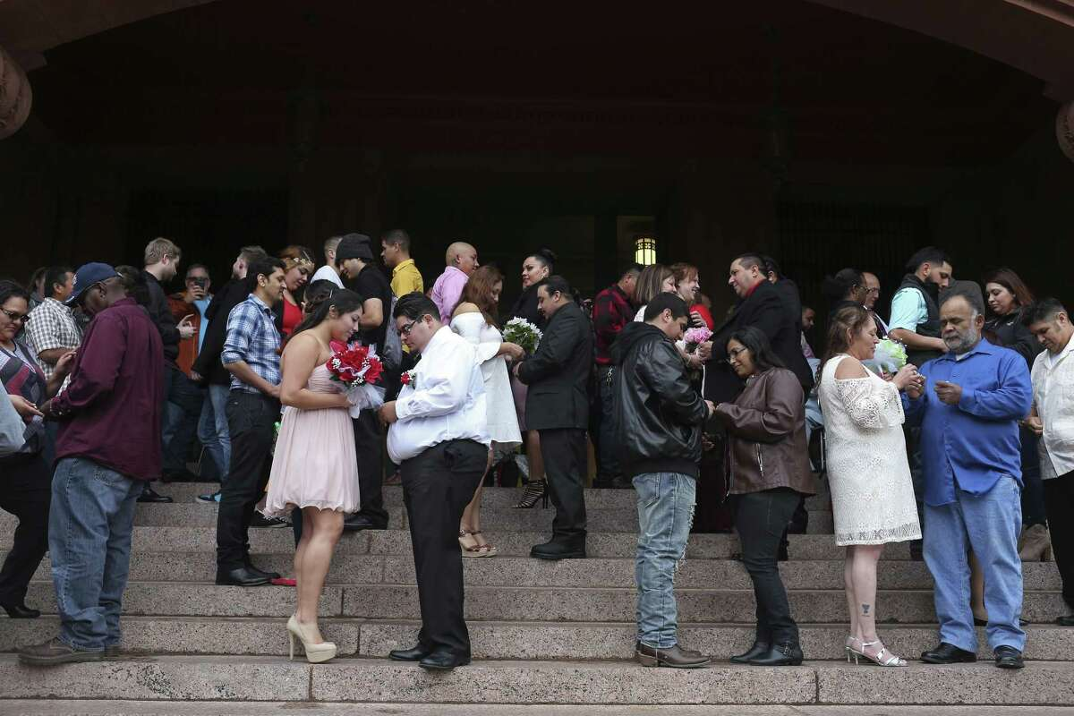 Couples exchanges rings during weddings in front of the Bexar County Courthouse on Valentine's Day, Feb. 14, 2017. Around 26 couples braved the cold winds to marry during the ceremony conducted by Bexar County Clerk Gerard Rickhoff.