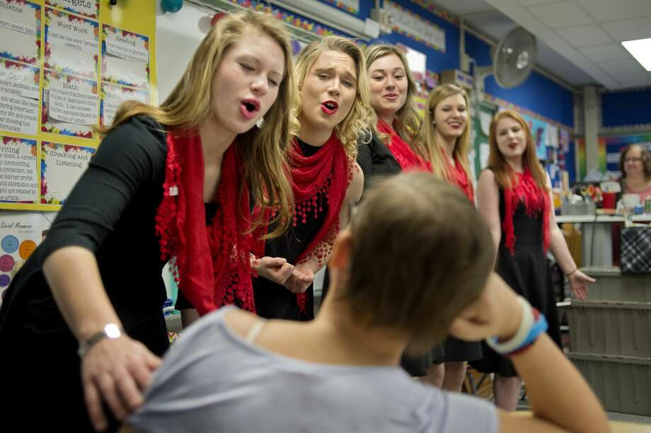 "BRITTNEY LOHMILLER | blohmiller@mdn.net Midland High School Meistersingers members from left: Irene Cline, Gloria Heye, Ashley Smith, Sheridan Seamster and Allison Smith sing ""One Call Away"" to Chestnut Hill fifth-grader Claire Cline during the groups annual singing Valentine fundraiser Tuesday morning. The Meistersingers sent groups around the area to sing to various people, businesses, schools and organizations chosen by community members who paid the group to sing, the funds are going towards a trip to Washington, D.C. this spring. Photo: Brittney Lohmiller/Midland Daily News/Brittney Lohmiller"