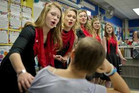 """BRITTNEY LOHMILLER   blohmiller@mdn.net Midland High School Meistersingers members from left: Irene Cline, Gloria Heye, Ashley Smith, Sheridan Seamster and Allison Smith sing """"One Call Away"""" to Chestnut Hill fifth-grader Claire Cline during the groups annual singing Valentine fundraiser Tuesday morning. The Meistersingers sent groups around the area to sing to various people, businesses, schools and organizations chosen by community members who paid the group to sing, the funds are going towards a trip to Washington, D.C. this spring."""