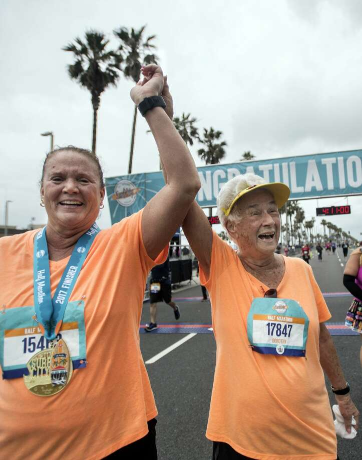 Jenny Dean, left,  and her mom Dorothy Joy, 90, celebrate finishing the Surf City Half Marathon on Sunday, Feb.  5, 2017 in Huntington Beach, Calif. (Mindy Schauer/Orange County Register/TNS) Photo: Mindy Schauer/TNS