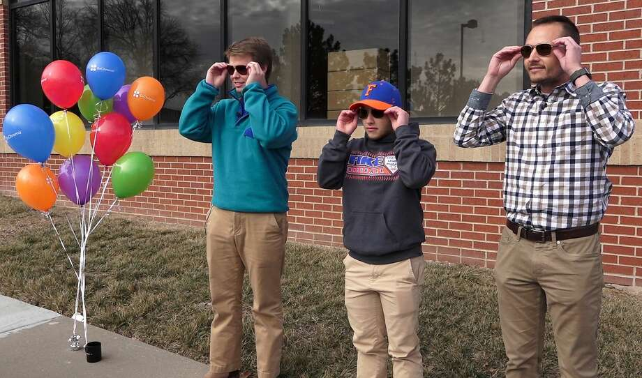 In Mission, Kan., one teen and two men fwith color vision deficiency, or color blindness, had the opportunity to see their world more vibrantly as they try on special EnChroma glasses. The lenses allow the wearer to experience more color saturation, distinguish certain colors better and see better detail and depth. From left, Austin Mitchell-Goering, Noah Vittengl and Ryan January try on the glasses at Brill Eye Center in Mission, Kan. (Jill Toyoshiba/Kansas City Star/TNS) Photo: Jill Toyoshiba/TNS