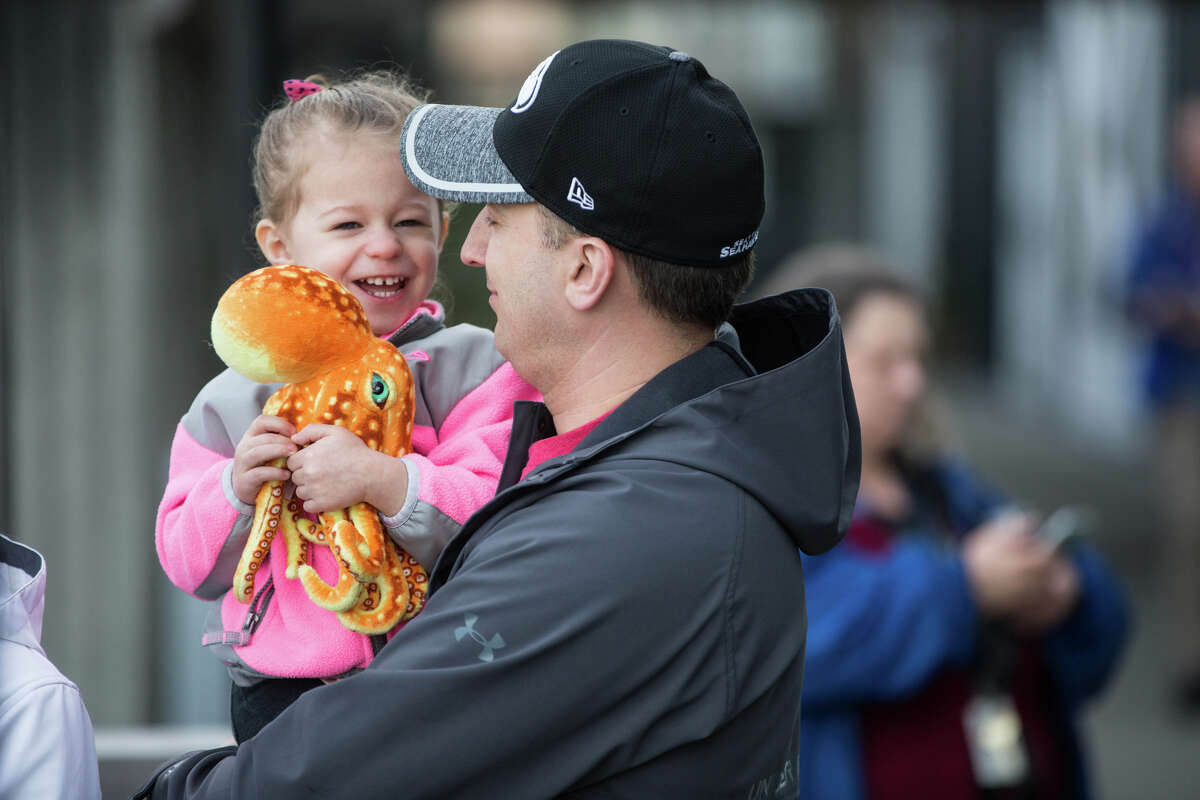 Mackenzie Hayford, 2, clutches a stuffed octopus toy while waiting for giant Pacific octopus