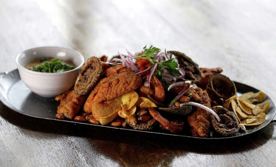 """The Super Jalea Platter, crispy fresh fried seafood mix, side of yucca sticks, rocto tartar sauce, """"salsa crilla"""" (red onions, lime, aji limo, cliantro) and canchita at Andes Cafe. Photo: James Nielsen, Houston Chronicle / © 2017  Houston Chronicle"""