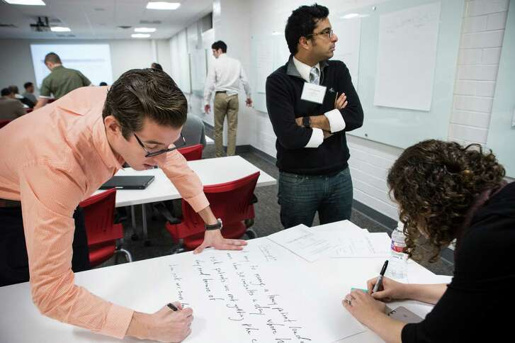 Juan Pablo Segura, left, and Anish Sebastian, both of BabyScripts, of Washington, D.C., work on a presentation during a workshop of the TMCx accelerator program at the Texas Medical Center on Tuesday, Feb. 14, 2017, in Houston. The TMCx accelerator program, focusing on health and hospital IT applications, began workshops with 24 new startups on Tuesday. ( Brett Coomer / Houston Chronicle )
