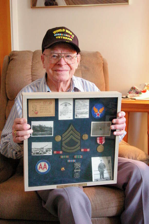 Niky House | for the Daily News Howard Shaver, who turns 100 today, poses with a shadow box containing keepsakes from his years of service in the U.S. Army.