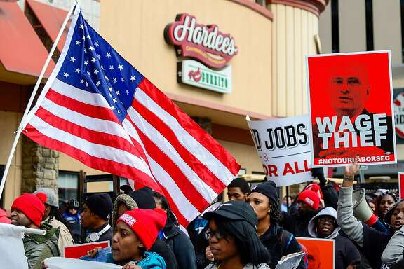 ST LOUIS, MO - FEBRUARY 13: Protesters rally against Labor nominee Andrew Puzder outside of a Hardee's restaurant on February 13, 2017 in St Louis, Missouri. The protesters feel that Mr. Puzder will not have the best interest of workers in mind due to his record of being a critic of raising the minimum wage as well as expansion of overtime pay, paid sick leave and the Affordable Care Act.   (Photo by Jeff Curry/Getty Images)